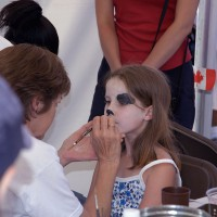 Girl having her face painted at Confederation Park during Canada Day celebration