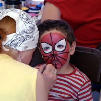 Boy having his face painted at Confederation Park during Canada Day celebration