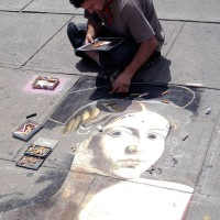 Artist drawing an image upside down on a sidewalk in the By Ward Market