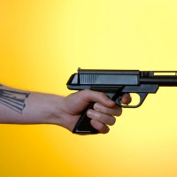 Man with tattoo holding a gun