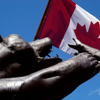 Sculpture of a bear catching a fish in front of Canadian flag