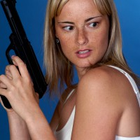 Woman with gun looking behind her