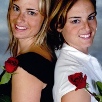 Twin sisters posing back to back holding roses
