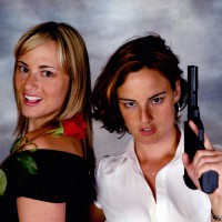 Twin sisters posing with a gun and a rose