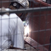 Welder welding metal beams