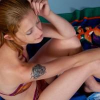 Woman in bikini sitting on beach towel