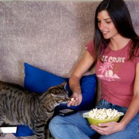 Woman giving popcorn to her cat