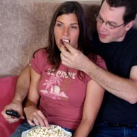 Man feeding popcorn to girlfriend