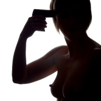 Model silhouette holding gun to her head