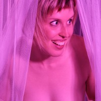 Topless woman peaking out of curtains
