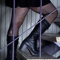 Girl in fish net stocking walking up stairs