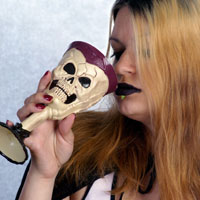 Gothic girl drinking from skull cup