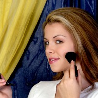 Pretty woman applying make-up
