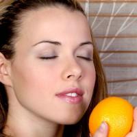 Pretty girl smelling an orange
