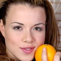 Pretty girl holding an orange