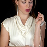 Beautiful woman holding a pearl necklace