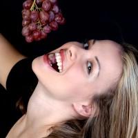 Beautiful woman eating grapes